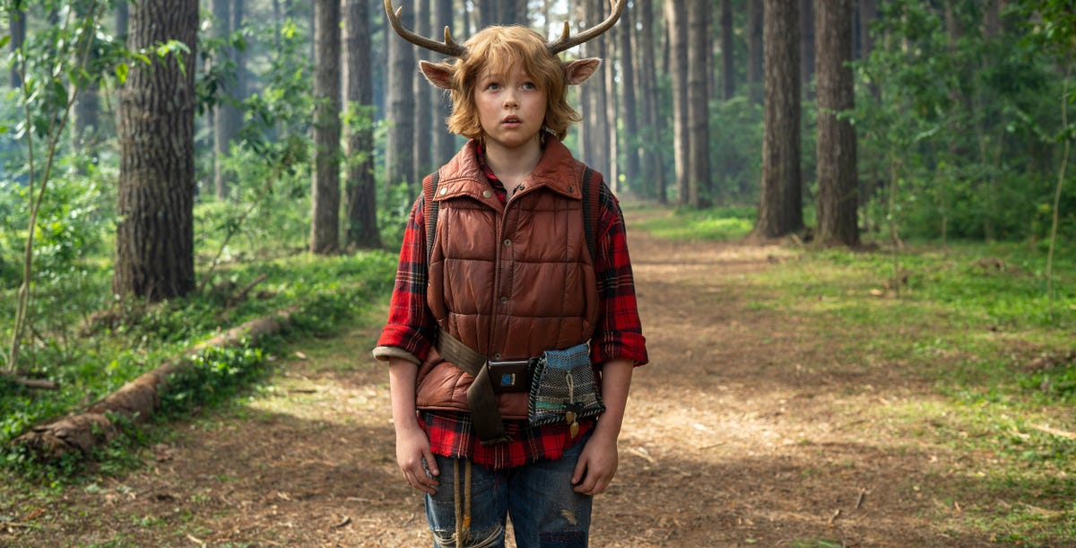 A boy with deer horns and ears stands in a forest.