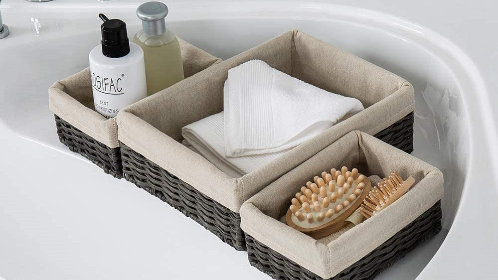 Pretty lined baskets sitting next to a sink.