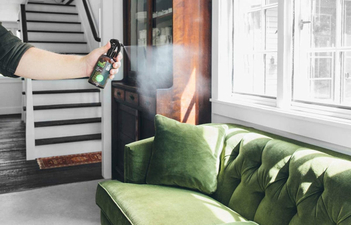 an arm spraying an odor eliminator product over a couch in a living room