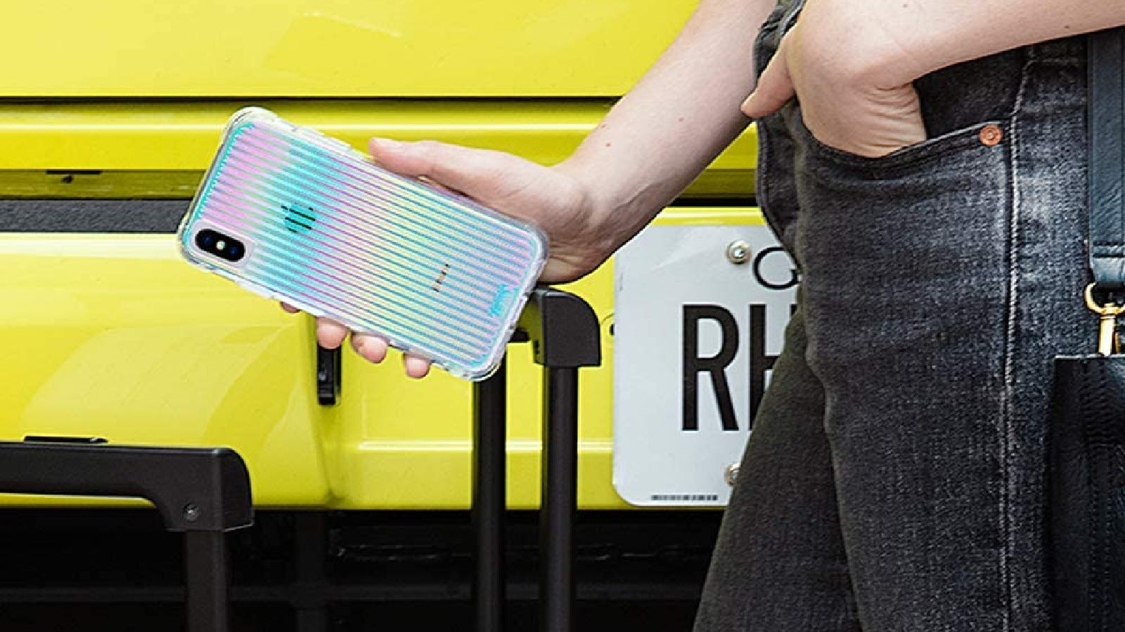 A woman holds her iPhone in its shiny and colorful case.