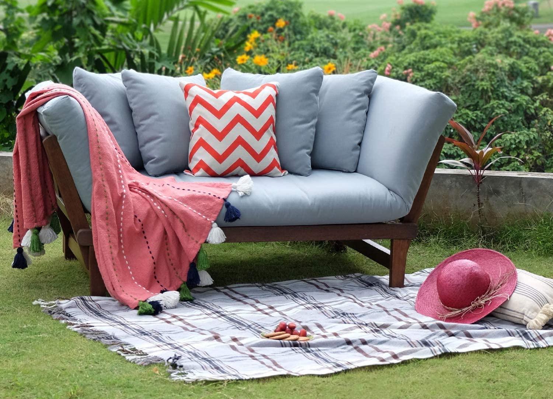 A small blue-gray cushy sofa on a green lawn