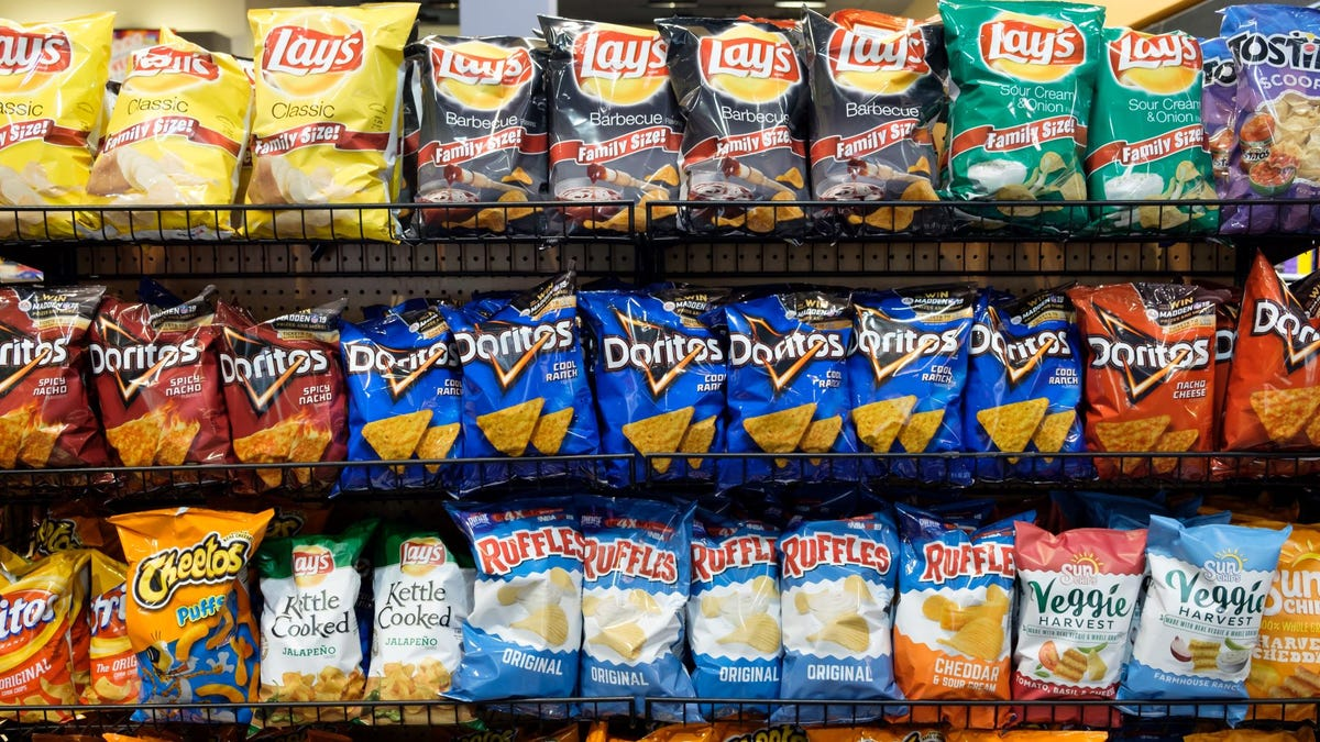 Lay's and Dorito's in a chip aisle at a grocery store.