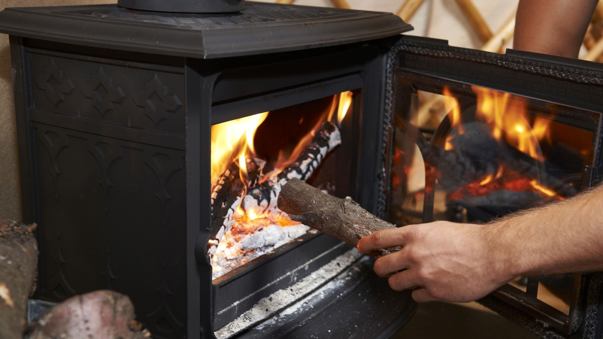 Someone putting a log in a woodburning stove.