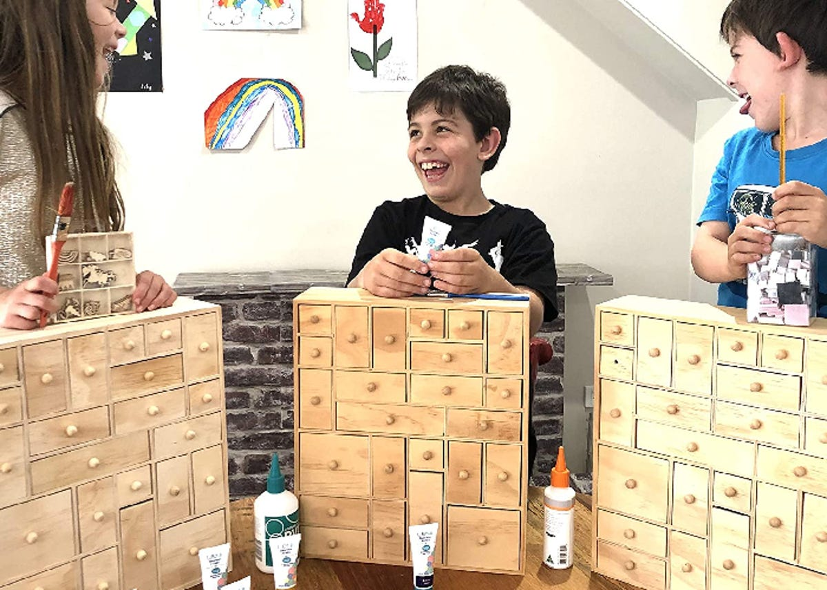 Three young kids play with craft supplies with a wooden teacher toolbox standing in front of each of them.