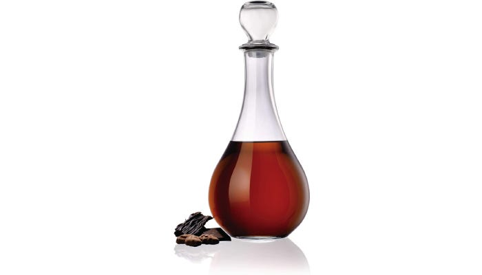 Tear-drop shaped decanter with a round stopper filled with red wine and chocolate candy on the left.