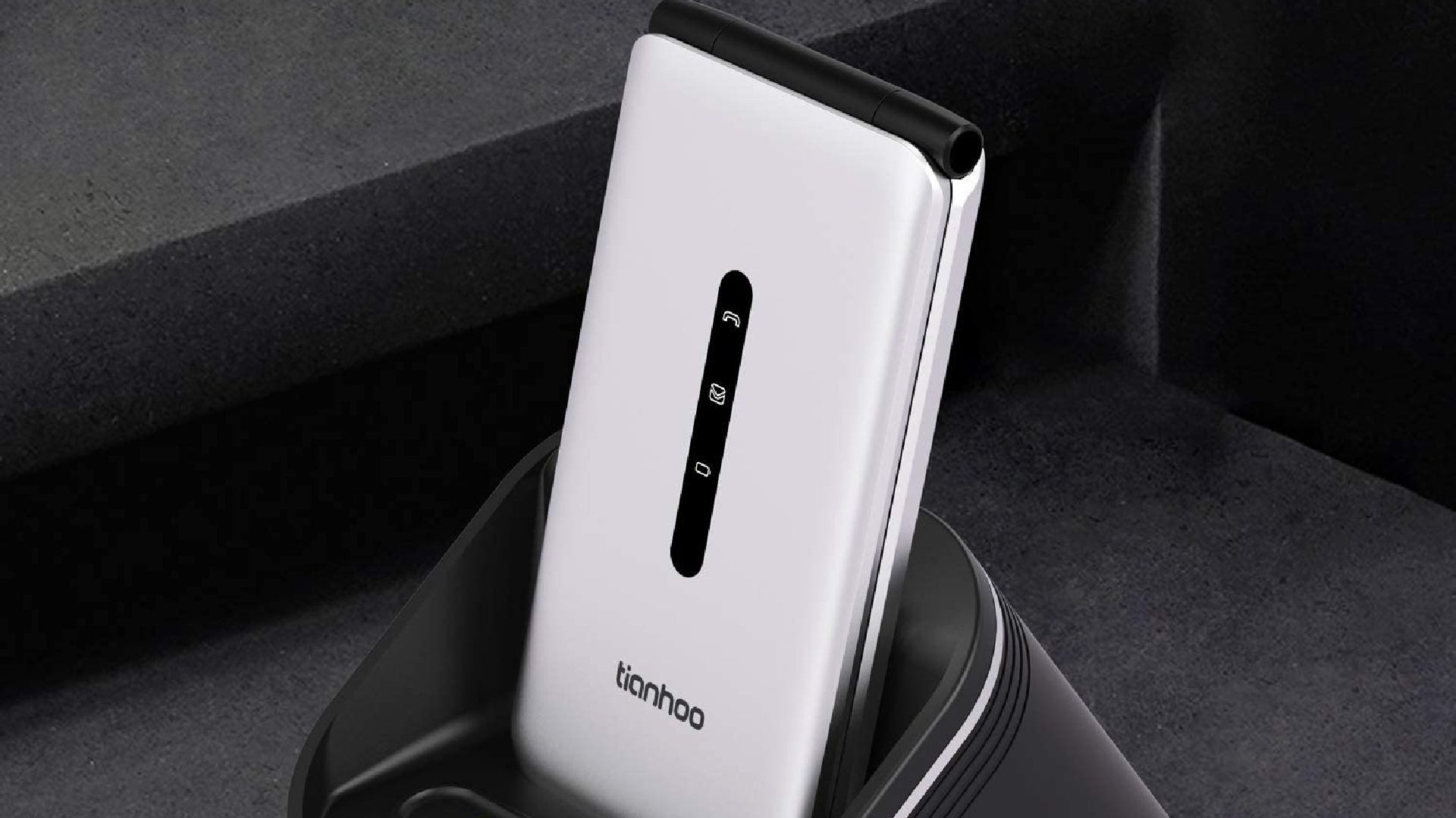 A white flip phone rests in its charging dock.