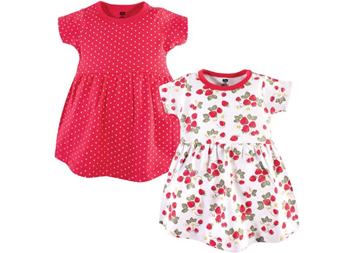 a little red dress with small white polka dots and a little white dress with strawberries