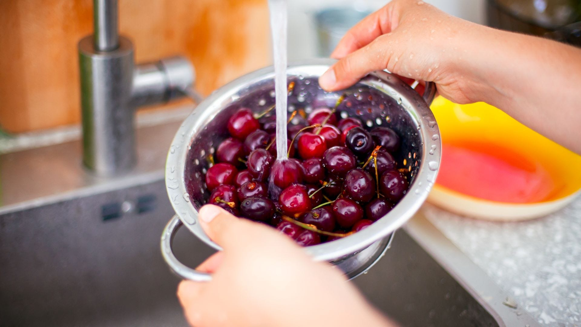 Someone rinsing a bowl full of cherries under a kitchen faucet.