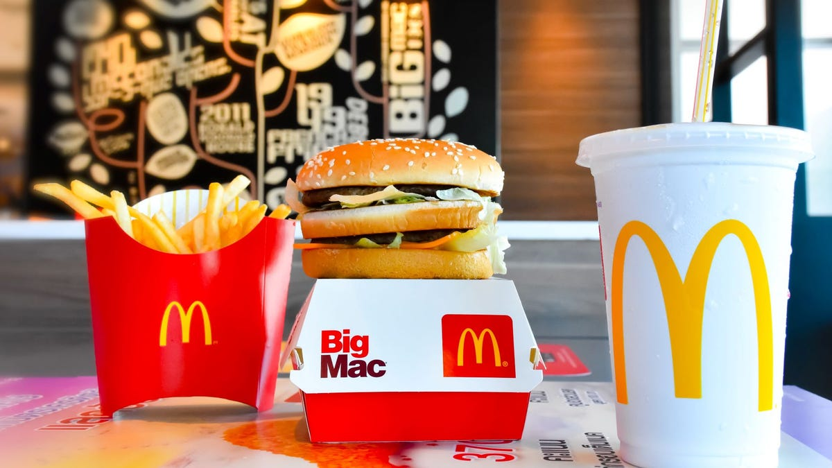 McDonald's fries, Big Mac, and soda combo meal on a table.