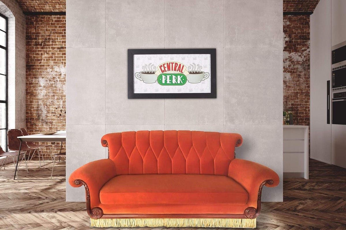 """A replica of the orange couch from """"Friends"""" with a """"Central Perk"""" sign hanging above it."""