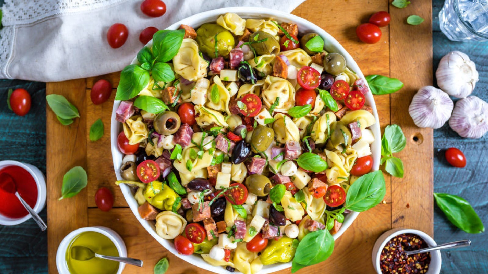 A big bowl of tortellini antipasto pasta salad with ingredients surrounding the bowl including cherry tomatoes, garlic, basil, pepper flakes etc.