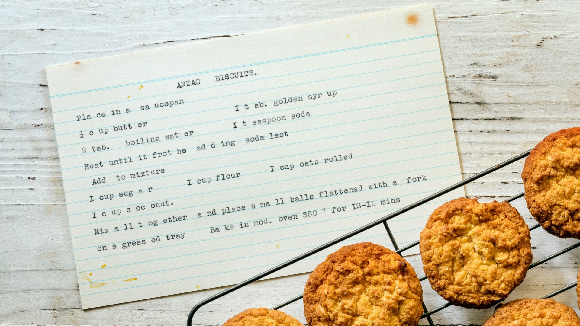 """A recipe for """"Anzac Biscuits"""" typed on an index card next to a rack full of them."""