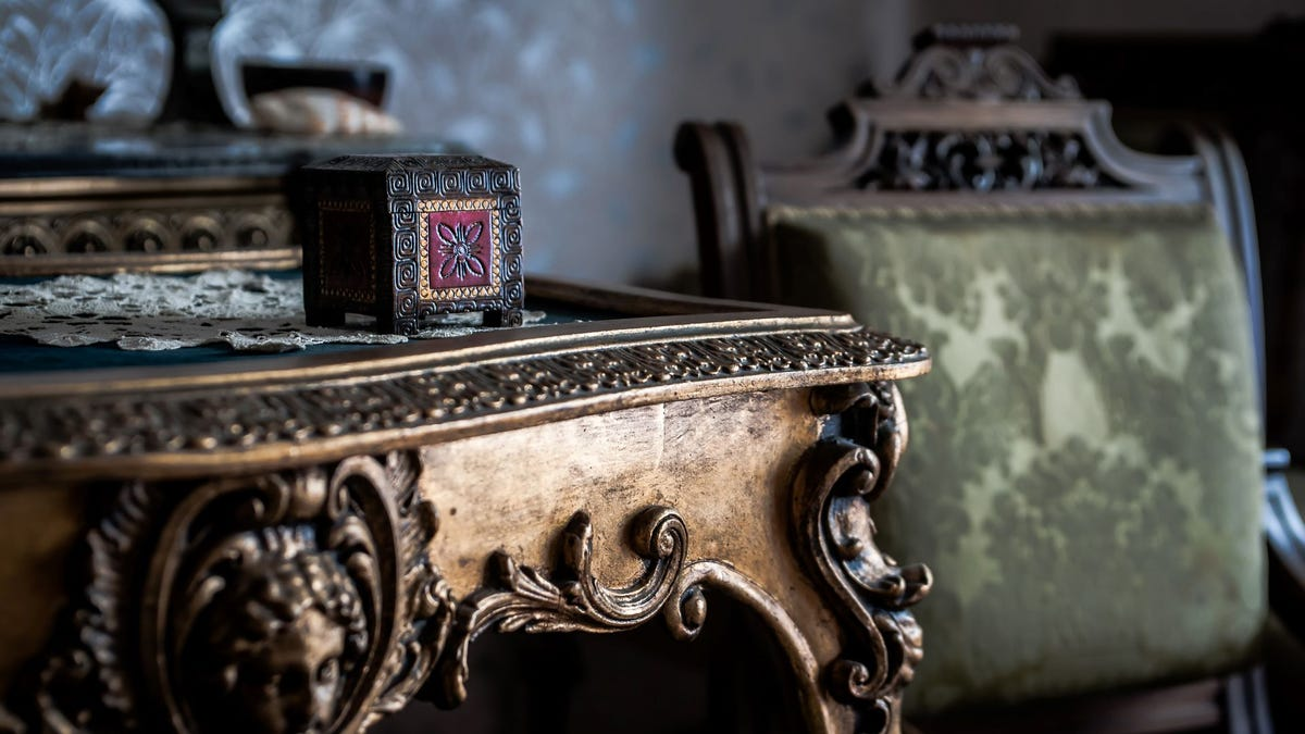 An antique side table and chair featuring carved wooden scrollwork.