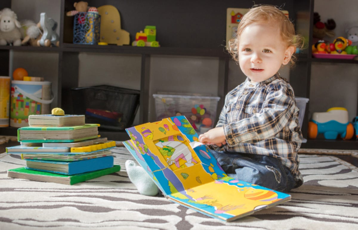 Happy sweet baby boy reading books sitting on the floor at home