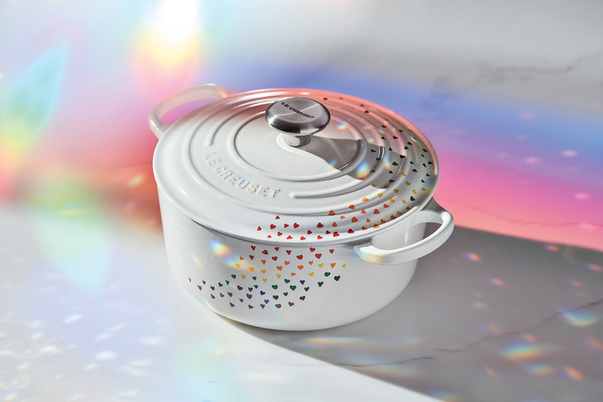 Le Creuset's new Dutch oven covered in hearts sitting on a neon-lit white countertop.