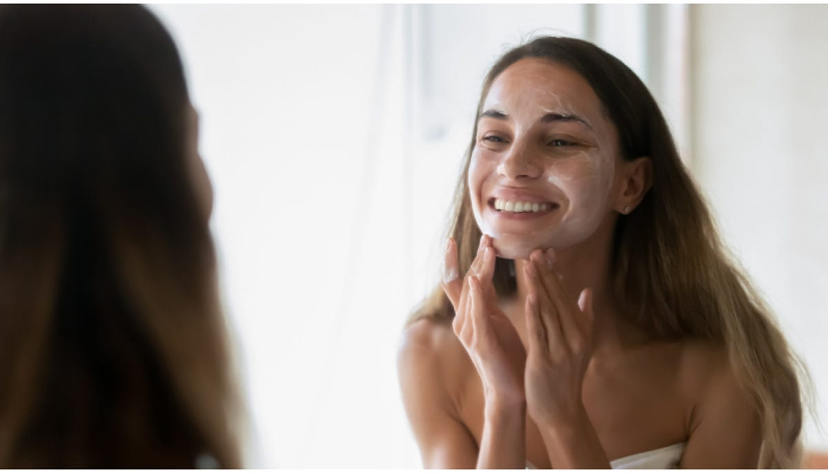 smiling young woman washing her face in the mirror
