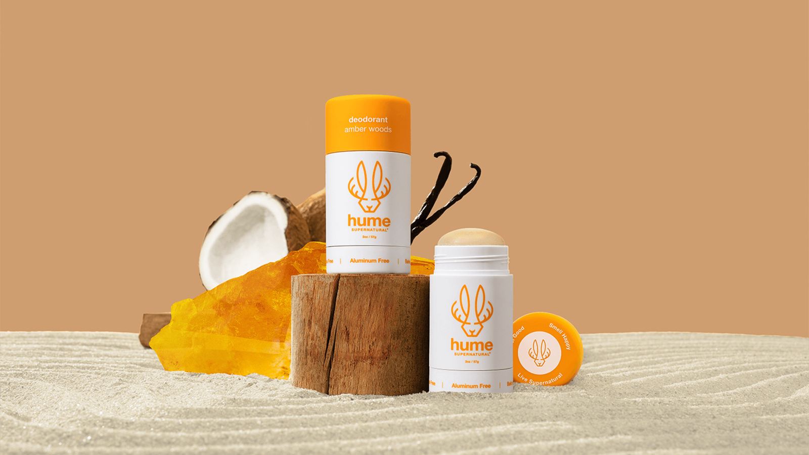 orange and white bottle of Hume deodorant on a piece of wood in the sand
