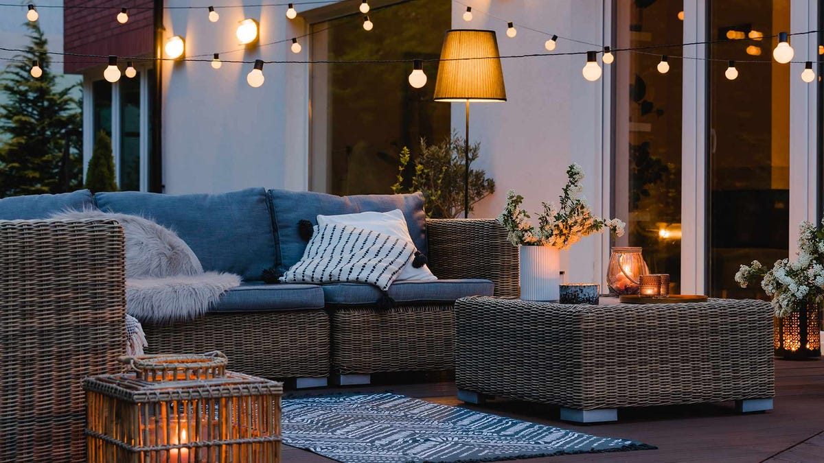 An outdoor living space with sofas, tables and mood lighting.