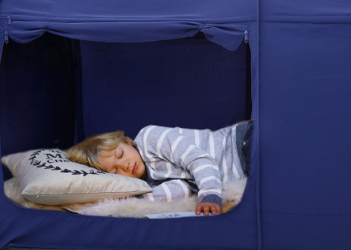 toddler peacfully sleeping in blue tent bed