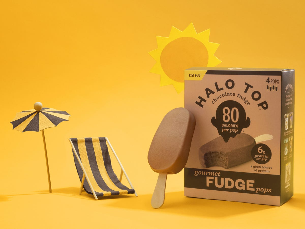 A tiny, striped beach chair and umbrella sitting next to a Halo Top Fudge Pop and its box.