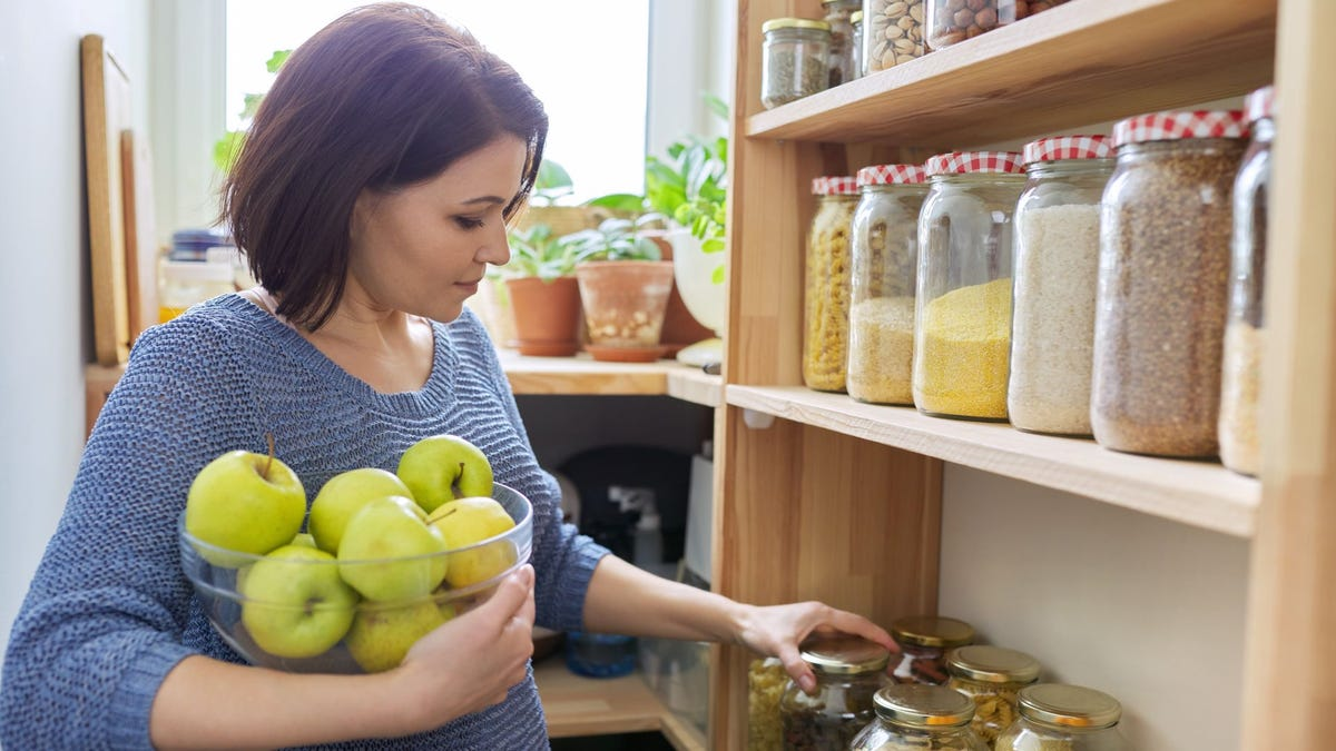 A woman holding a bowl of apples and picking a jar off the shelf in a pantry.