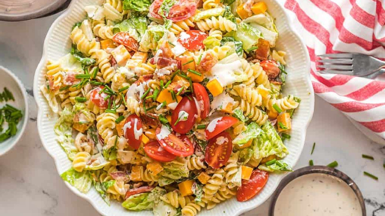 A large serving blow filled with BLT pasta salad, topped with fresh cherry tomatoes and chopped chives.