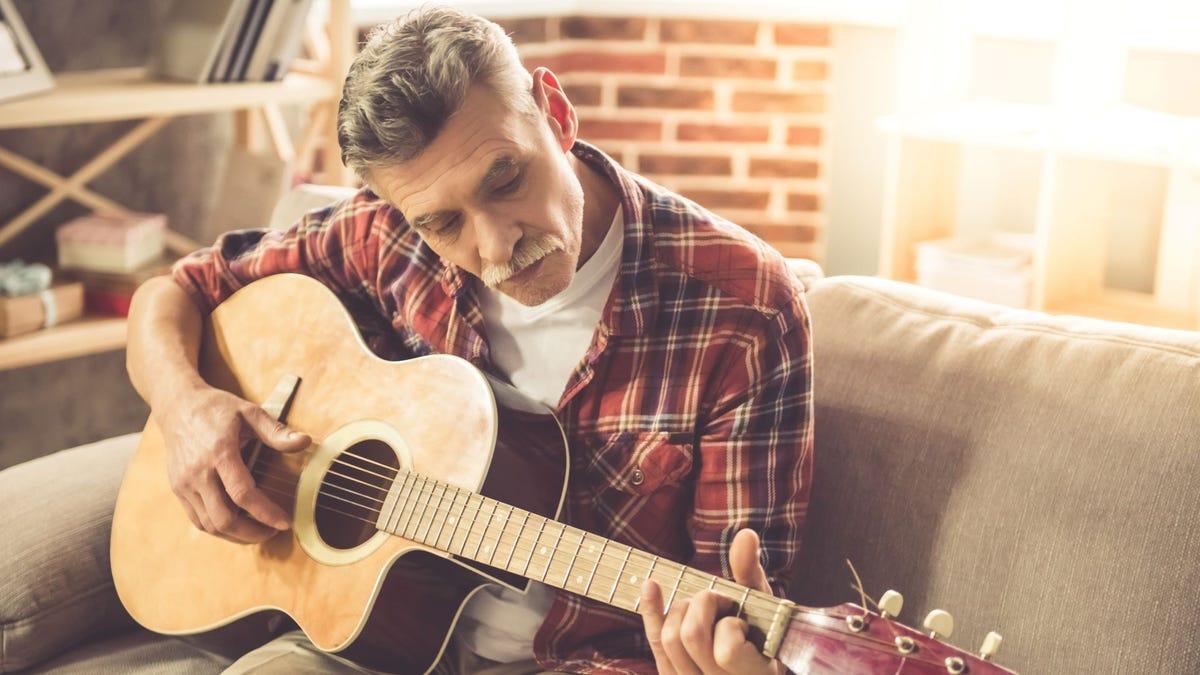 A mature man playing guitar.