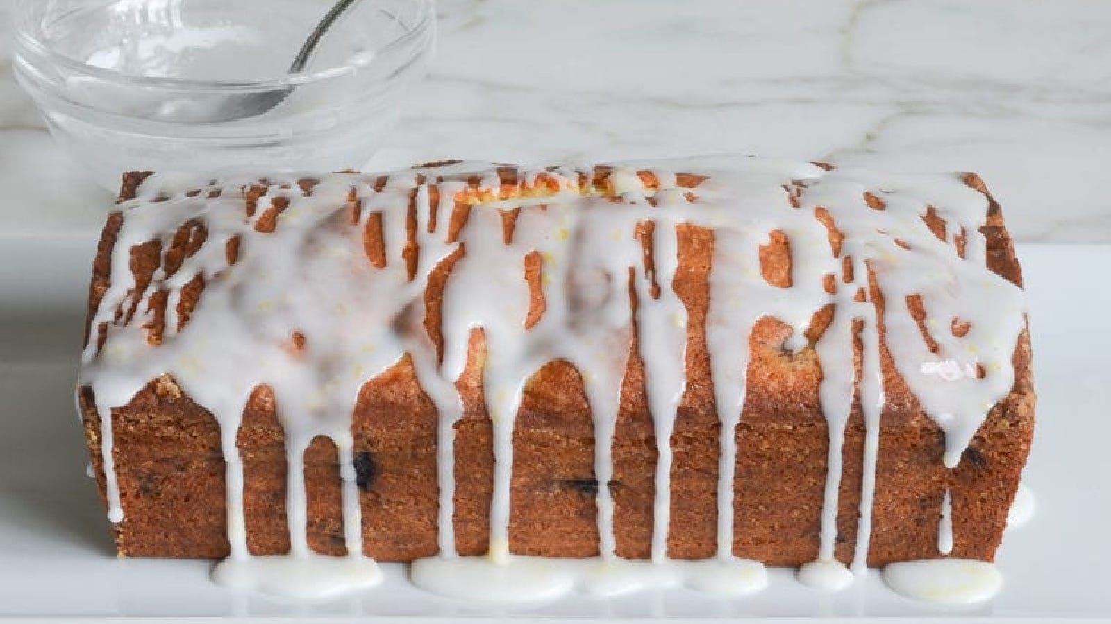A loaf of lemon blueberry pound cake drizzled with a homemade glaze.