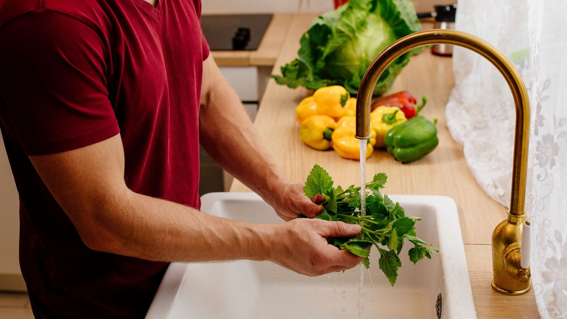 A man rinsing fresh mint leaves under a kitchen faucet.