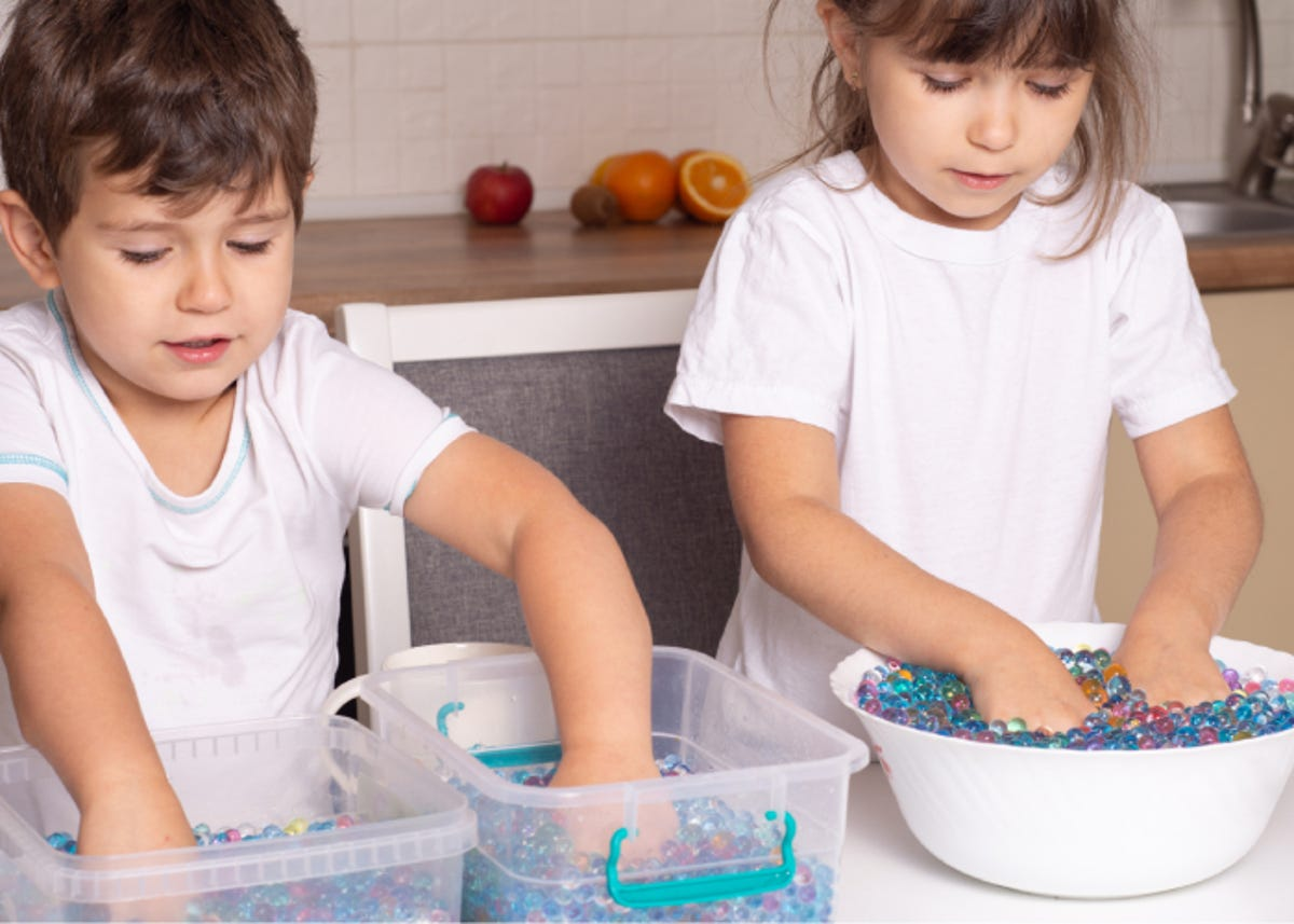 Two kids playing with colorful sensory water beads.