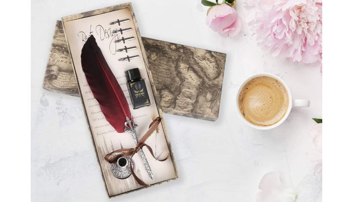A quill pen with a red feather and silver base sitting in its antique-style packaging next to a cup of coffee and pink flowers.