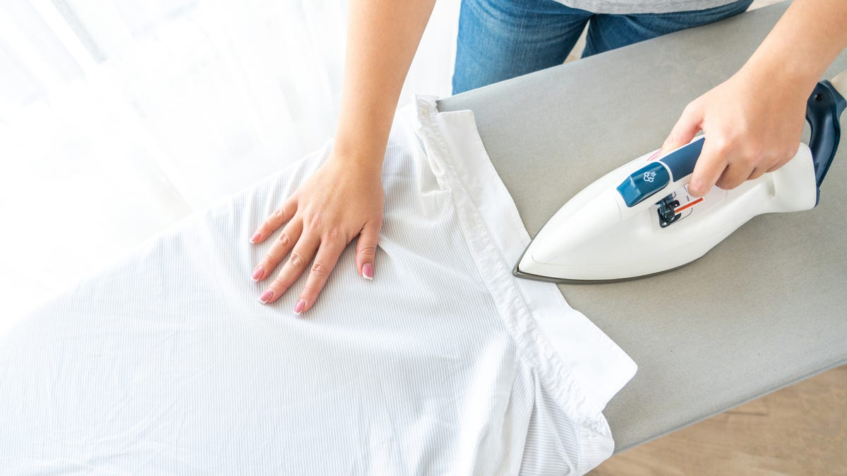 A woman holds a white shirt in place on an ironing board.
