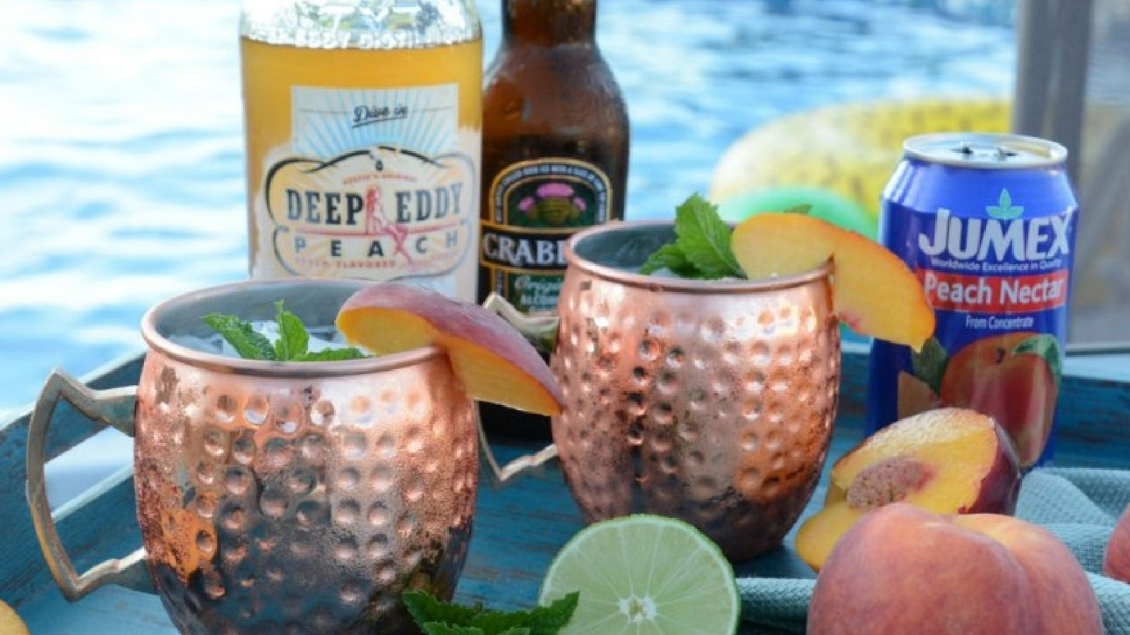 Two mule mugs filled with peach moscow mules, with peach vodka, ginger beer and peach nectar in the background.