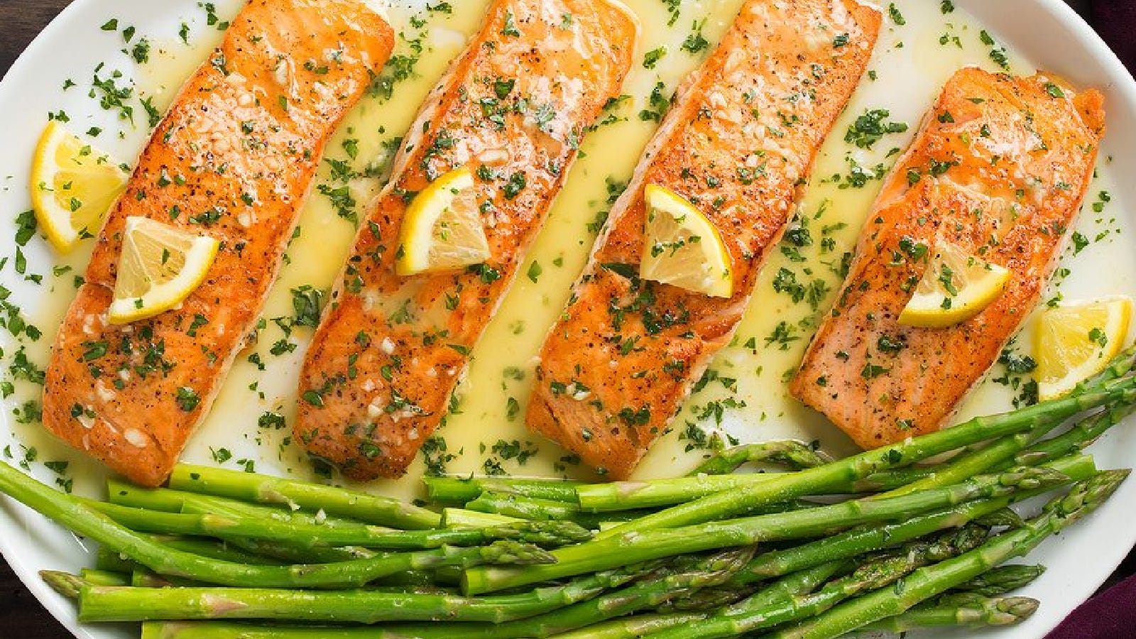 A large oval plate, plated with four salmon filets, with a side of asparagus, all covered with lemon butter sauce and garnished with lemon wedges.