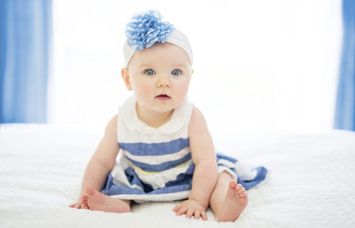 a baby girl in a blue and white striped dress and a headband sitting on a bed
