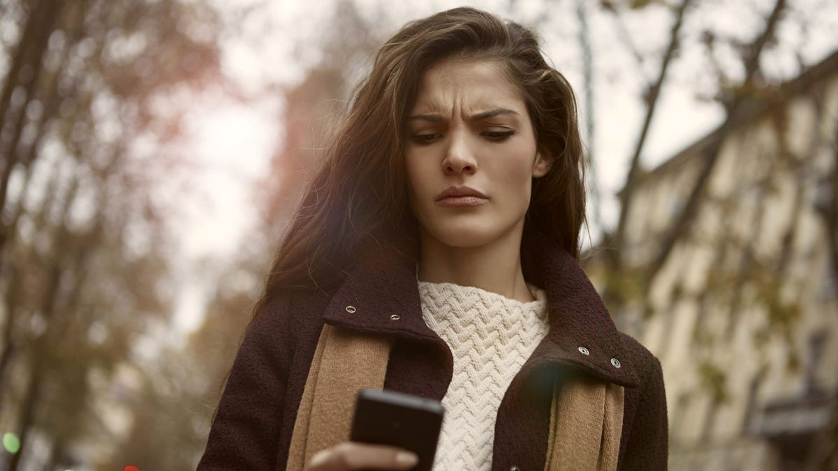 A woman looking at her phone with an angry expression.