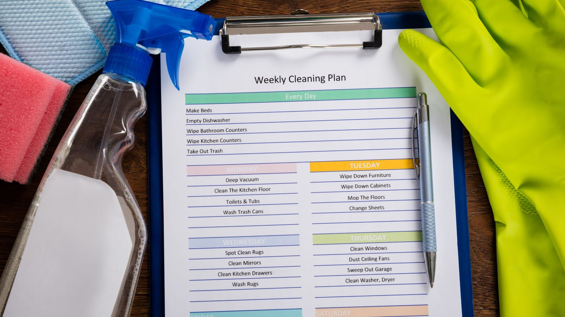 A weekly cleaning schedule on a clipboard surrounded by cleaning supplies.