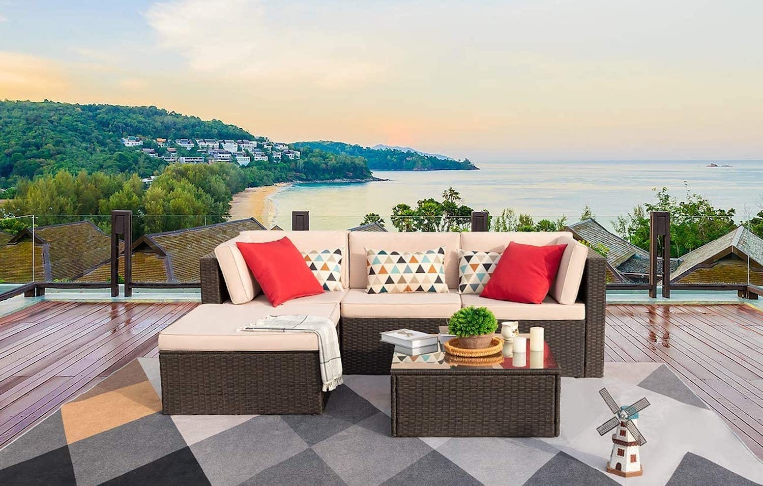 A beige patio sofa on a wood deck with a coastline in the background