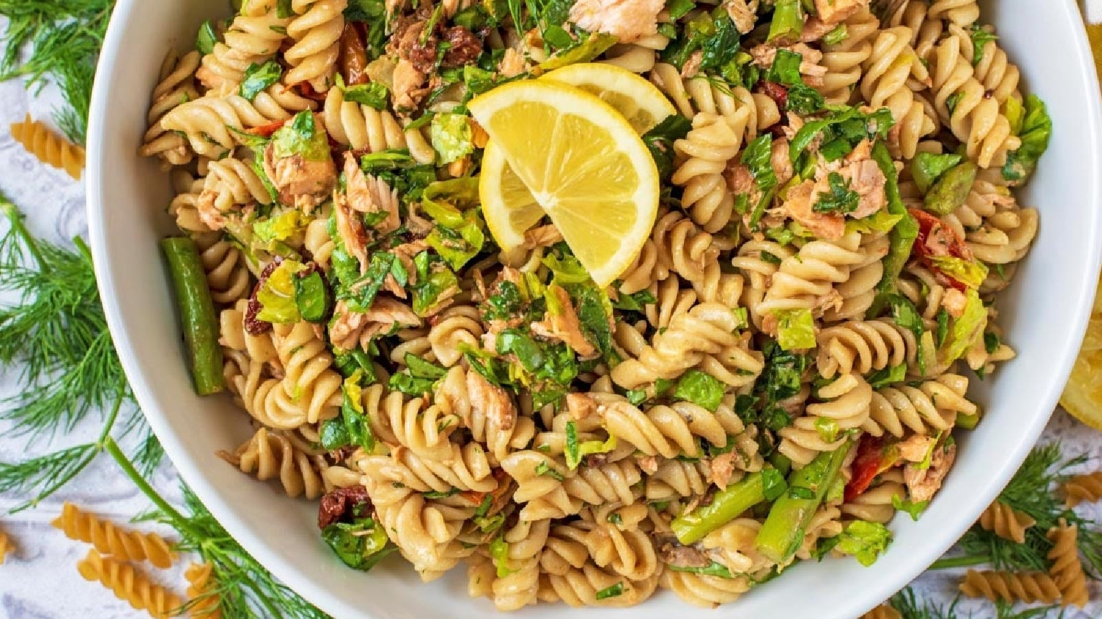 A large bowl full of rotini pasta salad with basil, asparagus and salmon garnished with lemon.
