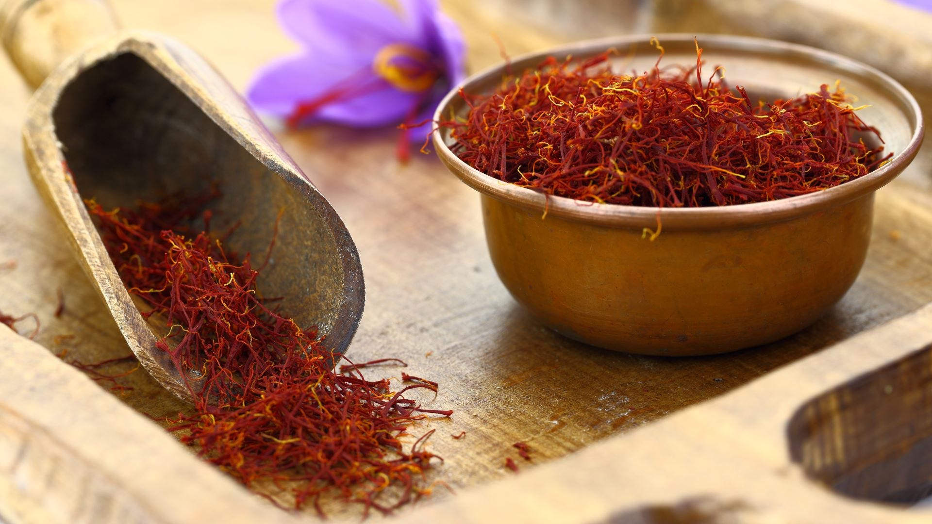 A bowl and scooper full of saffron next to a saffron flower.
