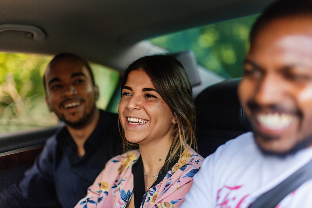 Three people smiling in an Uber.