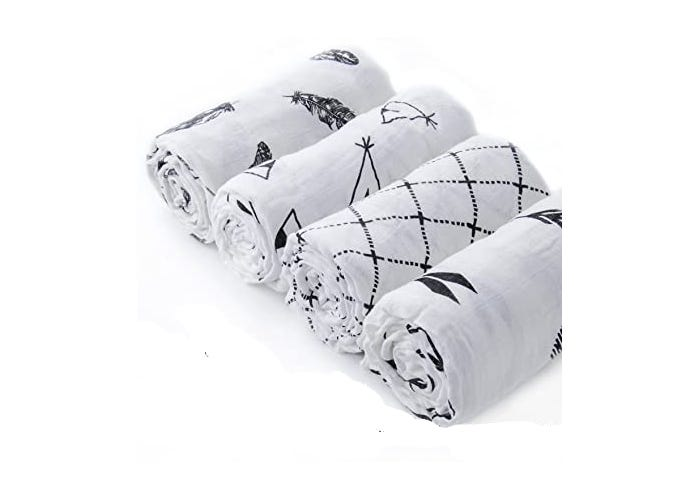 four rolled black and white printed blankets
