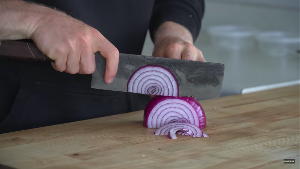 A man uses a knife to cut a red onion