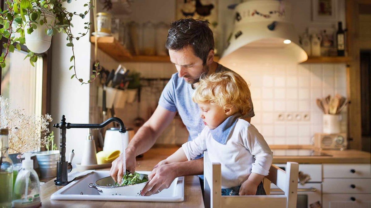 A father and his toddler wash vegetables in the sink and prepare a meal at home.