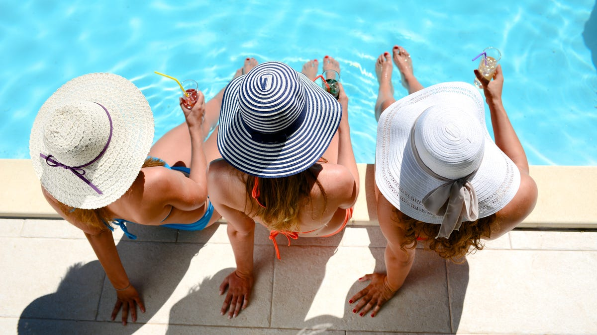 Three beautiful young woman with sun hats sitting by the poolside.