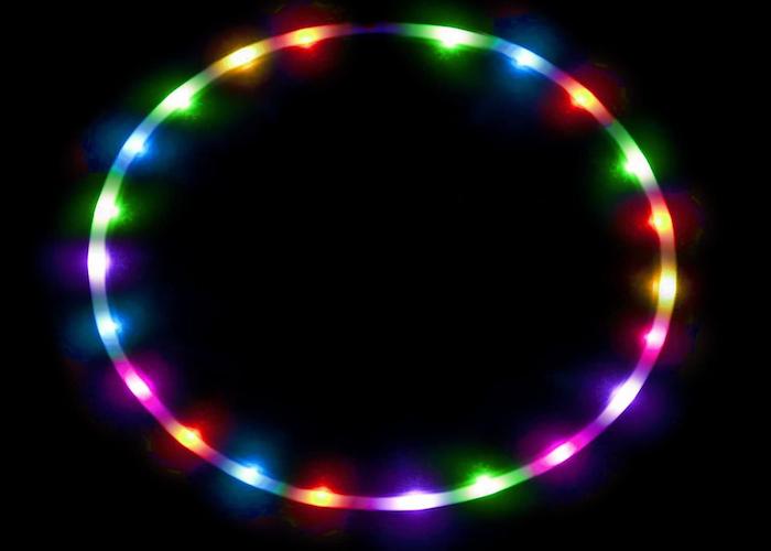 hula hoop lit up with rainbow LED lights on a black background