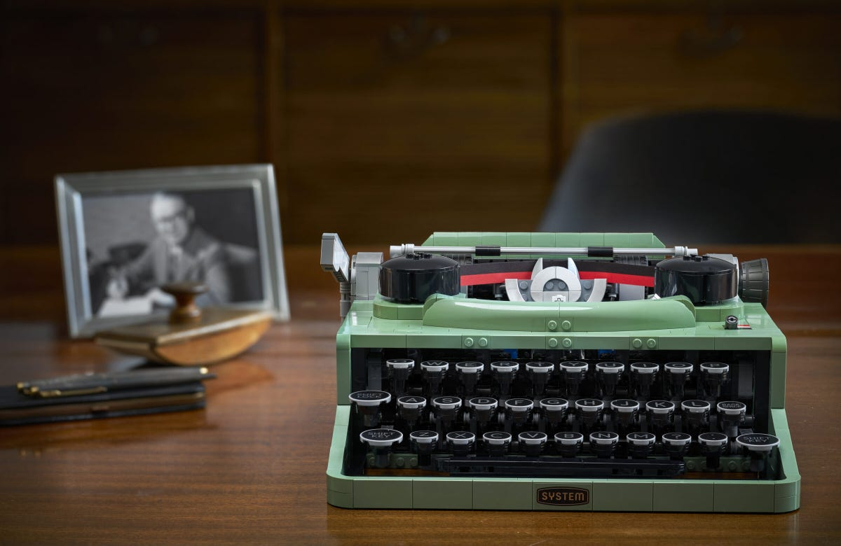 A teal green typewriter made of LEGO bricks sitting on a wooden desk.