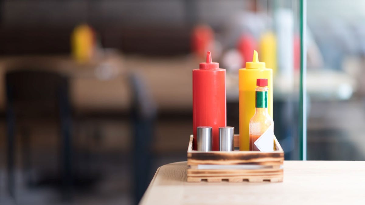 Condiments and hot sauce on a restaurant table.