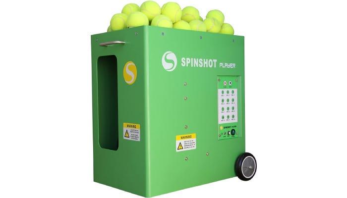 A green tennis ball machine filled with green tennis balls.