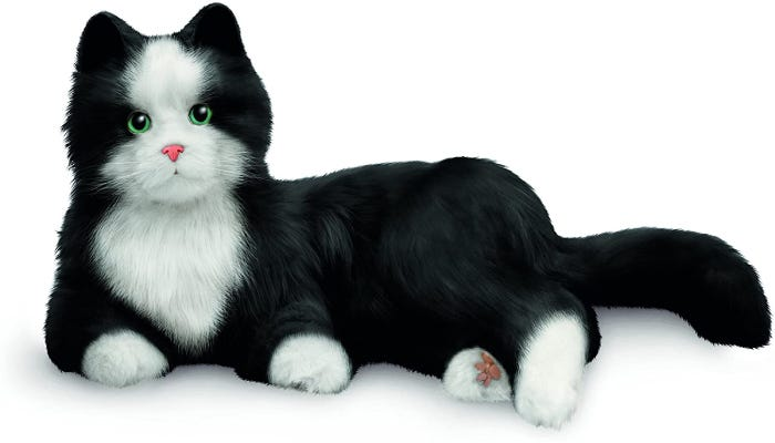 A black stuffed cat with white paws chest and patch on the face sits in a resting position.